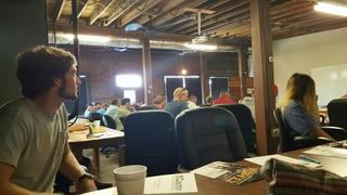 Production Crew Member Jonathan Lowder is intently listening to the morning meeting along with 53 of his coworkers.