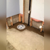 "A view of the SuperSump® sump pump. This sump system is installed with a flat lid so that this homeowner can essentially ""hide"" the system when refinishing. The discharge line runs out of the side of the basin and up behind the drywall."