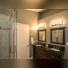 We worked closely with Edward and Sharon to designed a custom bathroom that had everything they wanted and needed in it. Here is a view of the door and you can see the glass shower and custom double sink vanity we installed in their Odenton home.