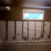 Within this photo you can see that the CleanSpace® vapor barrier has been installed along the back wall of the basement. Any water entering from the wall will run down behind the vapor barrier and into the (soon  to be) installed WaterGuard® system.