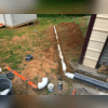 The French drain has been installed and the discharge pipe is being laid.