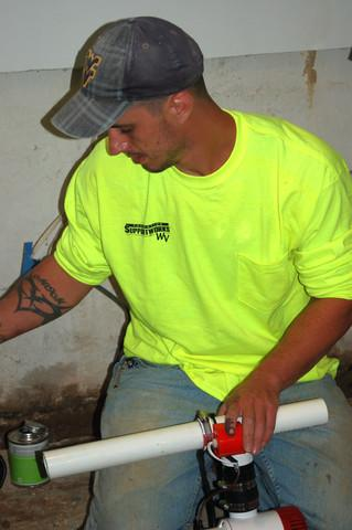 Foreman Marcus Gibbs works to install a sump pump in the basement of a customer's home in Bridgeport.